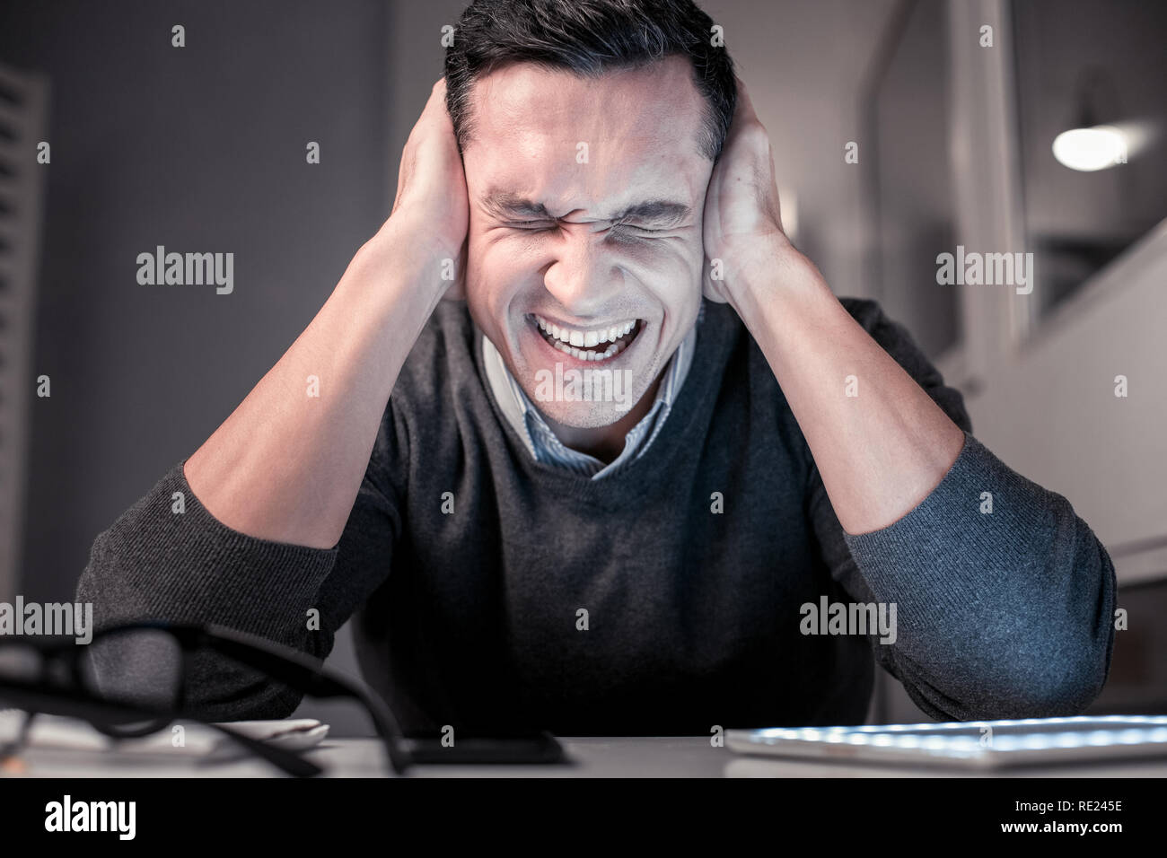 Unhappy cheerless man covering his ears with hands - Stock Image