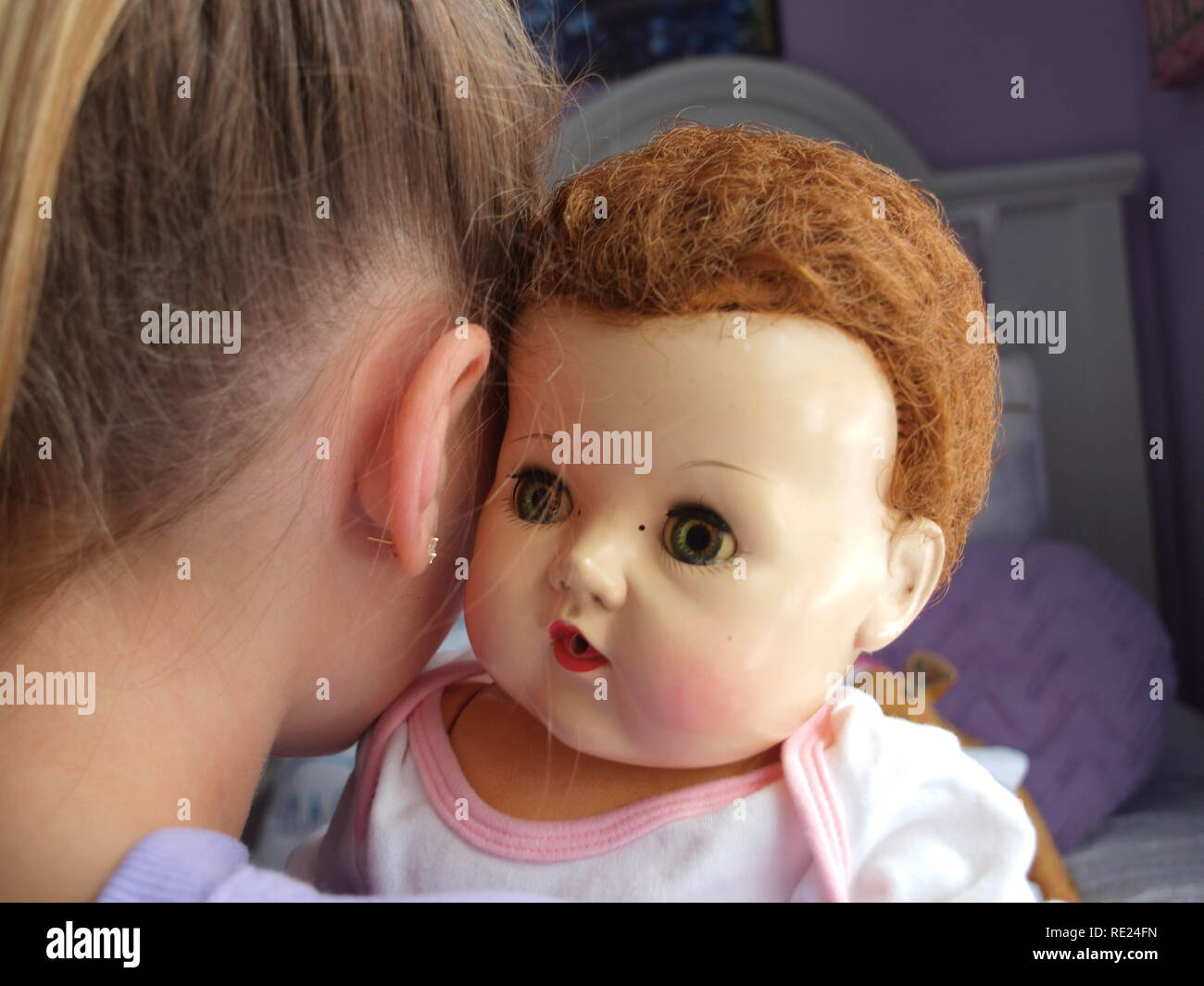 This images includes on original Tiny Tears doll which has been handed down from the young girls grandmother to her. The doll is original piece. Stock Photo