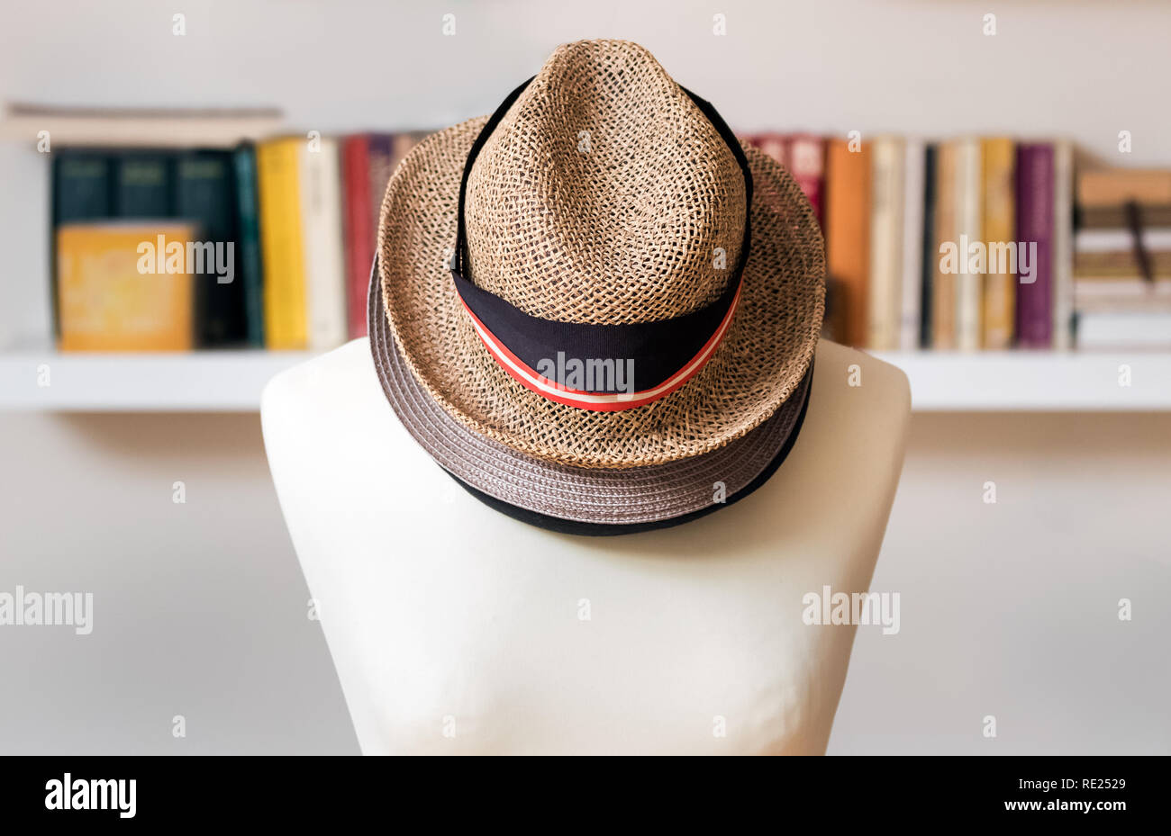 Three hats one on top of the other on a mannequin at home. - Stock Image