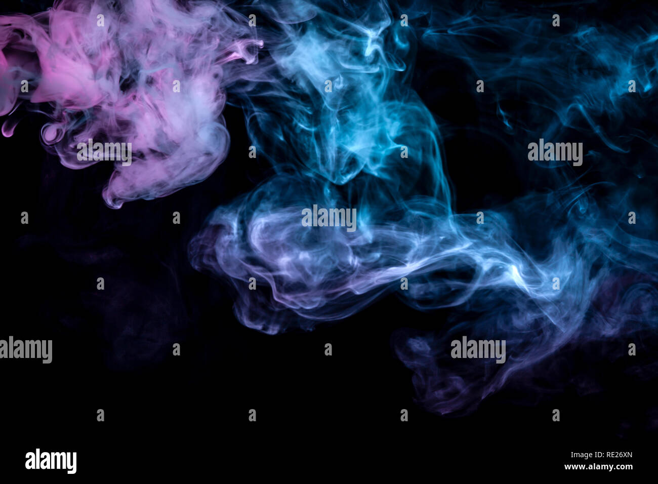 Clouds of isolated colored smoke: blue, red, green, pink; scrolling on a black background in the dark close up. Stock Photo