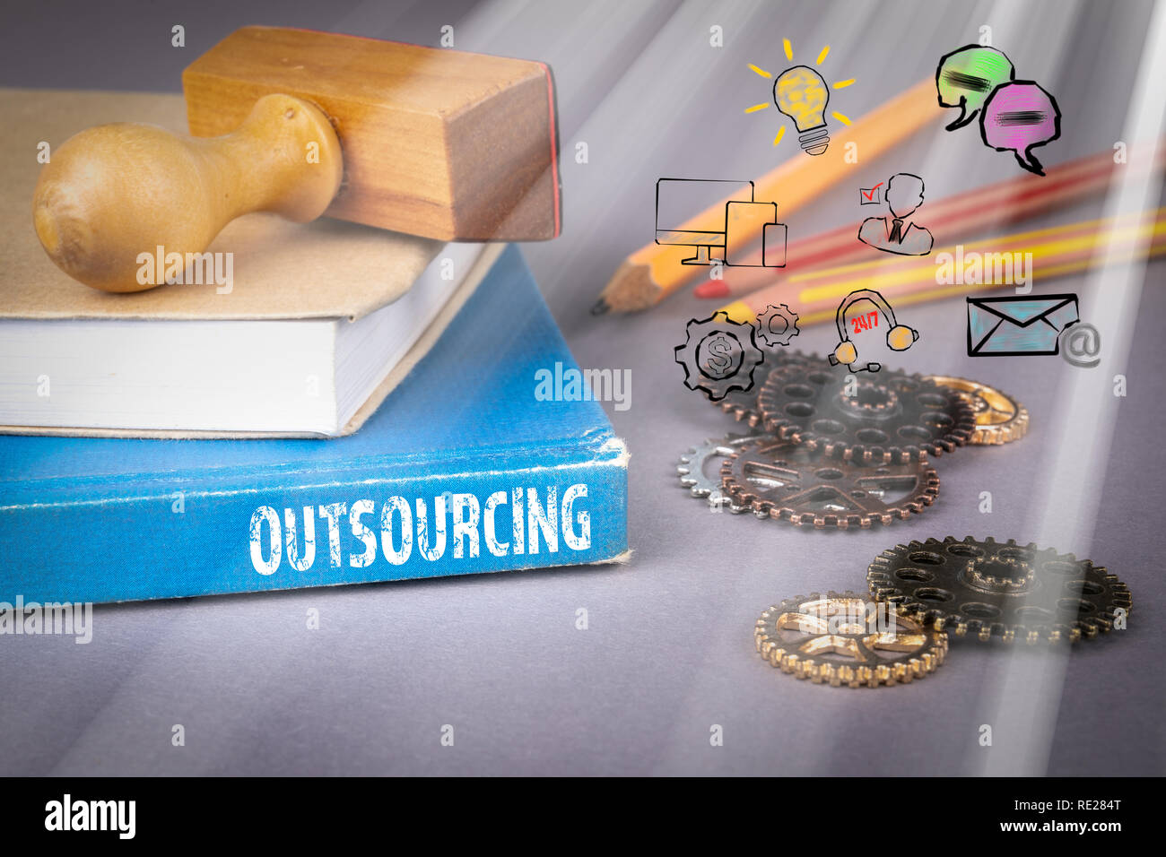 Outsourcing concept. blue book on a gray office table - Stock Image