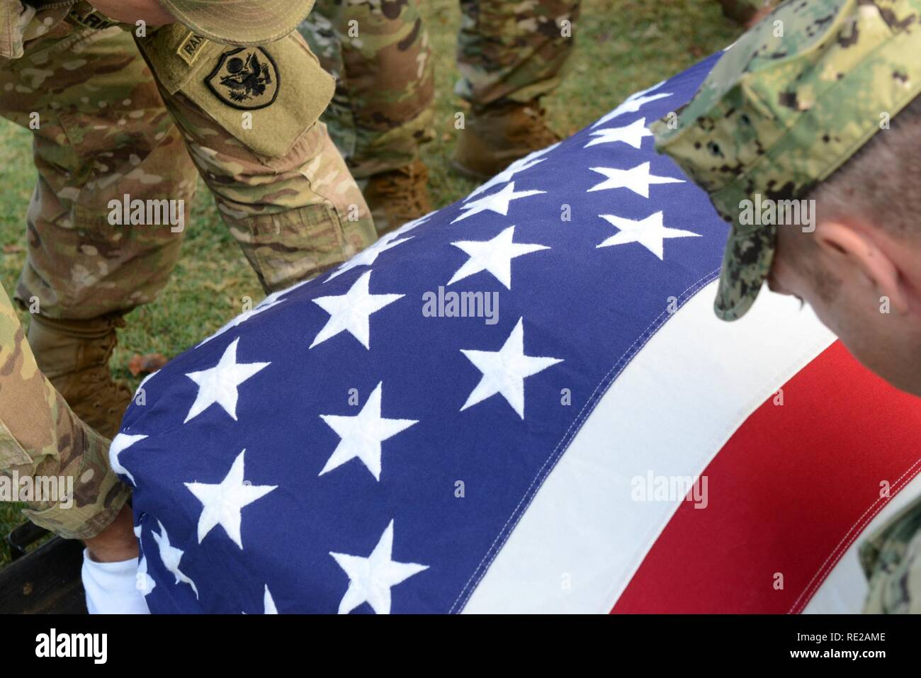Members of the Defense POW/MIA Accounting Agency (DPAA) honor guard detail drape the American Flag over a disinterred casket during the disinterment ceremony for unknown U.S. Marines from the battle at Tarawa at the National Memorial Cemetery of the Pacific, Honolulu, Hawaii, Nov. 7, 2016. The remains will be transferred to the DPAA laboratory for identification. DPAA's mission is to provide the fullest possible accounting for our missing personnel to their families and the nation. Stock Photo