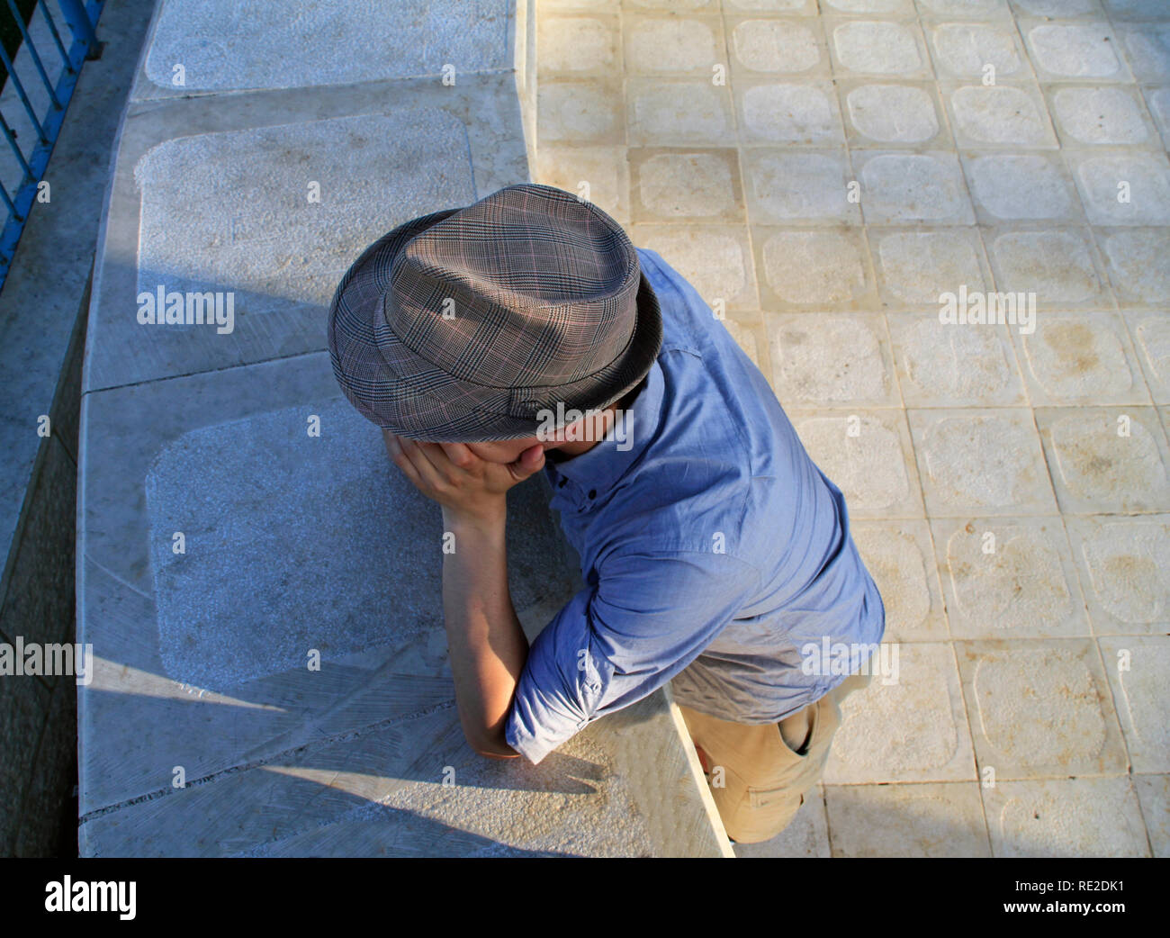 Man with a fedora, with his head resting on his hands seen from a high angle - Stock Image