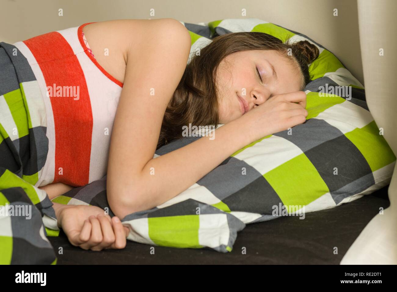 Teenage girl is sleeping at home in bed. - Stock Image