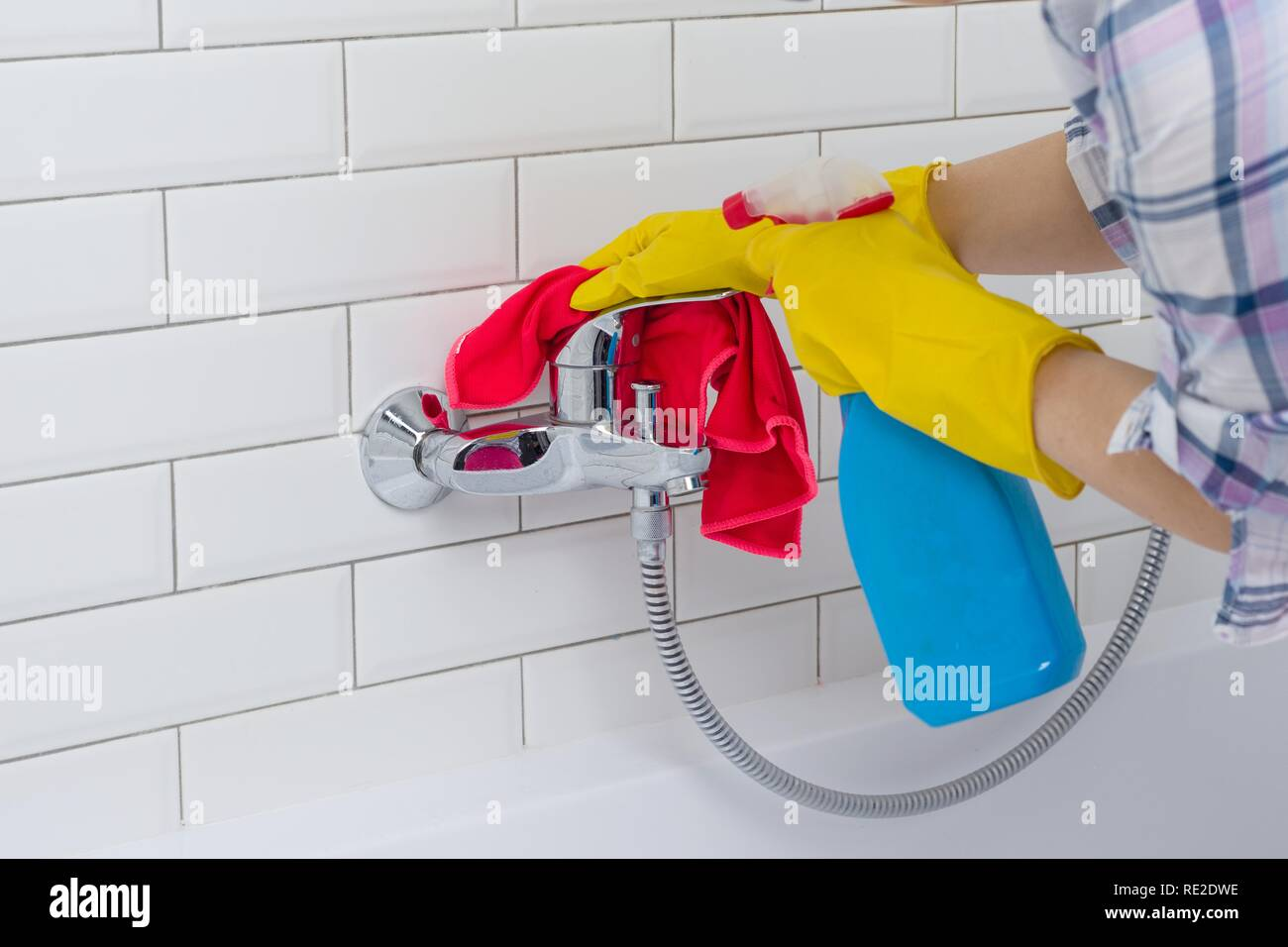 Housework and domestic lifestyle. Woman doing chores in bathroom at home, cleaning wash basin and tap with spray detergent. Stock Photo