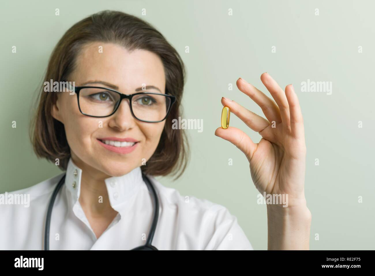 Female doctor takes vitamin capsule. Healthy lifestyle, nutritional supplements, vitamin d, e, fish oil capsules. Stock Photo