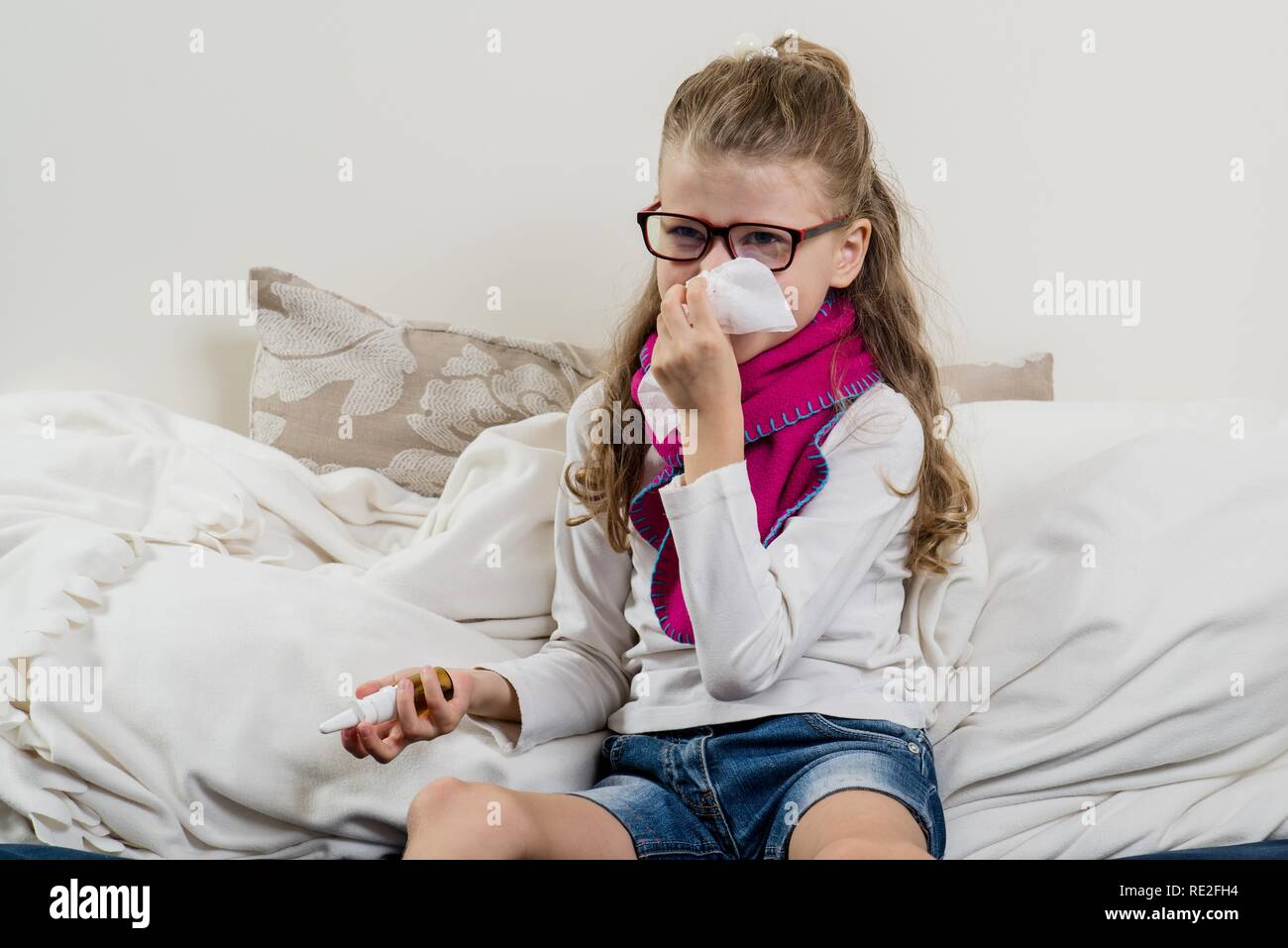 Cute  young girl child in glasses sneezing in a tissue blowing his runny nose - Stock Image