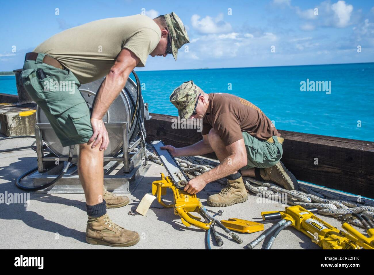 Chief Petty Officer Jesse Hamblin, right, and Petty Officer 1st Class Christopher Chilton, both assigned to Underwater Construction Team (UCT) 2's Construction Dive Detachment Bravo (CDDB), replace the chain on a hydraulic chainsaw in Diego Garcia, British Indian Ocean Territory,  Nov. 8, 2016.  CDDB is performing precision underwater demolition and light salvage to remove obstructions from Diego Garcia's deep draft wharf. CDDB is on the third stop of their deployment, where they are conducting inspection, maintenance, and repair of various underwater and waterfront facilities while under Comm Stock Photo
