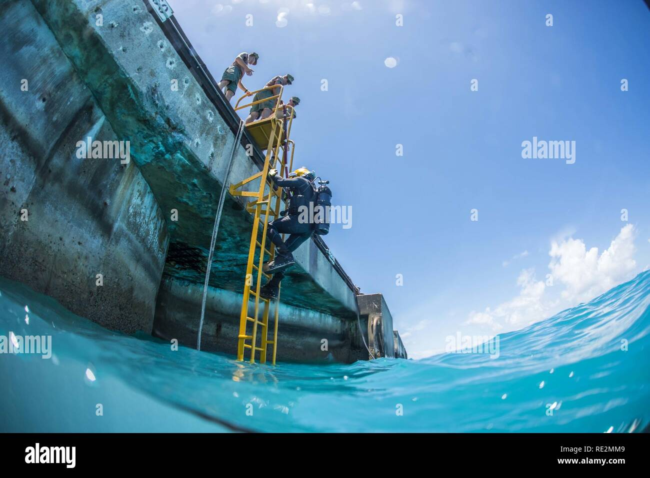 Chief Petty Officer Jesse Hamblin, assigned to Underwater Construction Team (UCT) 2's Construction Dive Detachment Bravo (CDDB), descends the diving ladder while conducting diving operations in Diego Garcia, British Indian Ocean Territory, Nov. 8, 2016.  CDDB is performing precision underwater demolition and light salvage to remove obstructions from Diego Garcia's deep draft wharf. CDDB is on the third stop of their deployment, where they are conducting inspection, maintenance, and repair of various underwater and waterfront facilities while under Commander, Task Force (CTF) 75, the primary ex Stock Photo