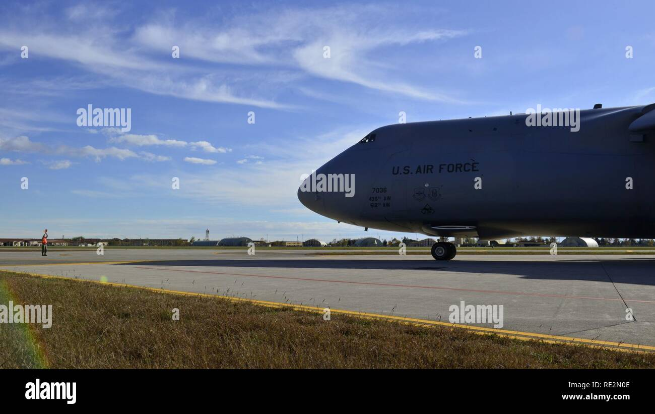 A C-5M Super Galaxy taxis into position for cargo loading at Aviano Air Base, Italy on Nov. 8, 2016. 724th Air Mobility Squadron personnel loaded all-terrain vehicles and other cargo to Iraq. - Stock Image