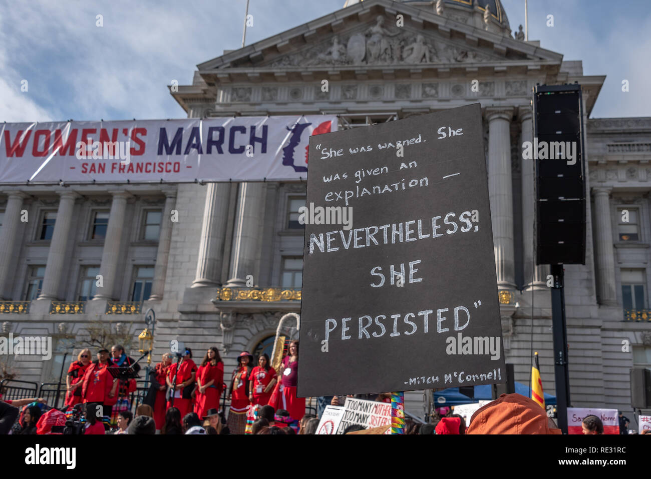 San Francisco, USA. 19th January, 2019. The Women's March San Francisco begins with a rally at Civic Center Plaza in front of City Hall. A sign held high above the crowd bears Mitch McConnell's quote from his attempt to silence Elizabeth Warren: 'She was warned. She was given an explanation - nevertheless, she persisted.' A sign above the crowd  Credit: Shelly Rivoli/Alamy Live News - Stock Image