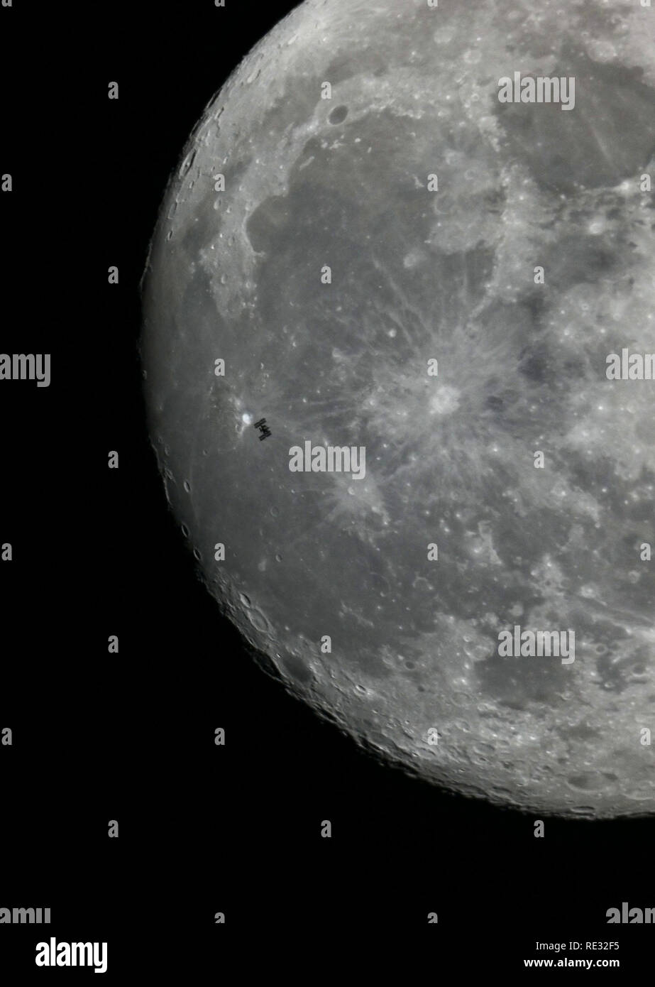 20 January 2019, North Rhine-Westphalia, Köln: The International Space Station ISS passes the moon and thus becomes visible for a short time as a silhouette. Photo: Henning Kaiser/dpa Credit: dpa picture alliance/Alamy Live News - Stock Image