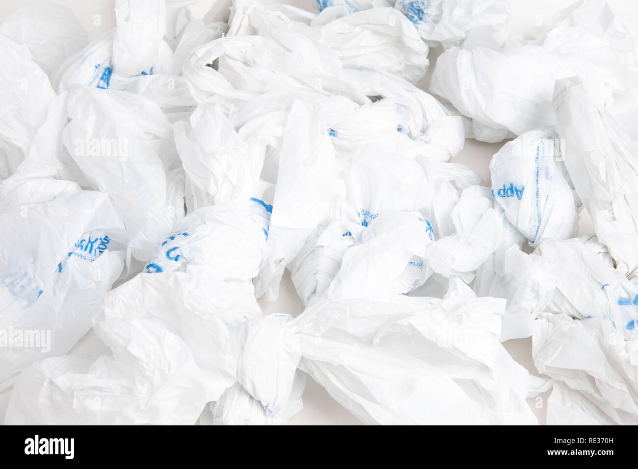 A bunch of crumpled white disposable plastic with blue prints. - Stock Image