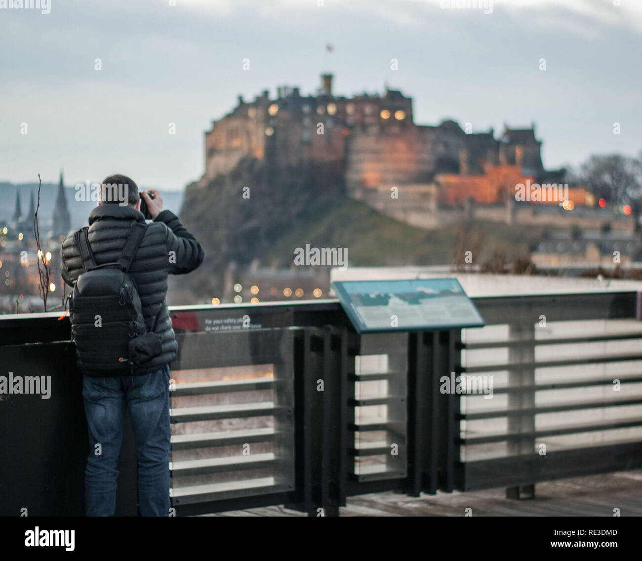 A photographer (foreground) taking a picture of Edinburgh's Castle from a roof top terrace. Travel photography. Tourism Stock Photo