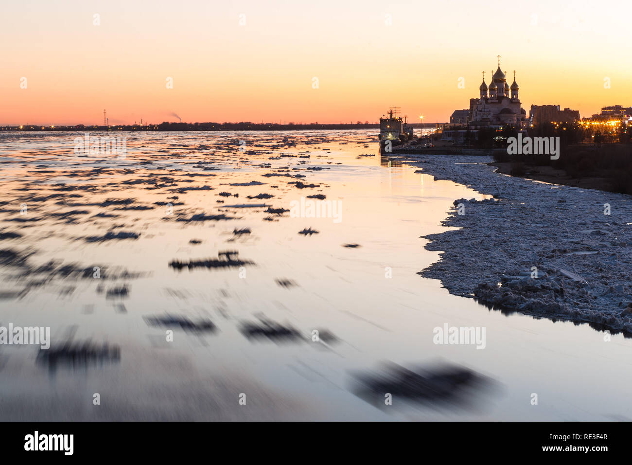 Ice drift in Northern Dvina river in Arkhangelsk, Russia. Beautiful ice motion evening landscape. - Stock Image