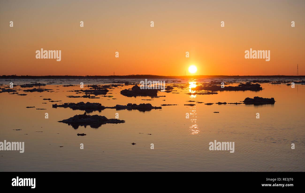 Ice drift on sunset. . Beautiful ice motion evening landscape. - Stock Image