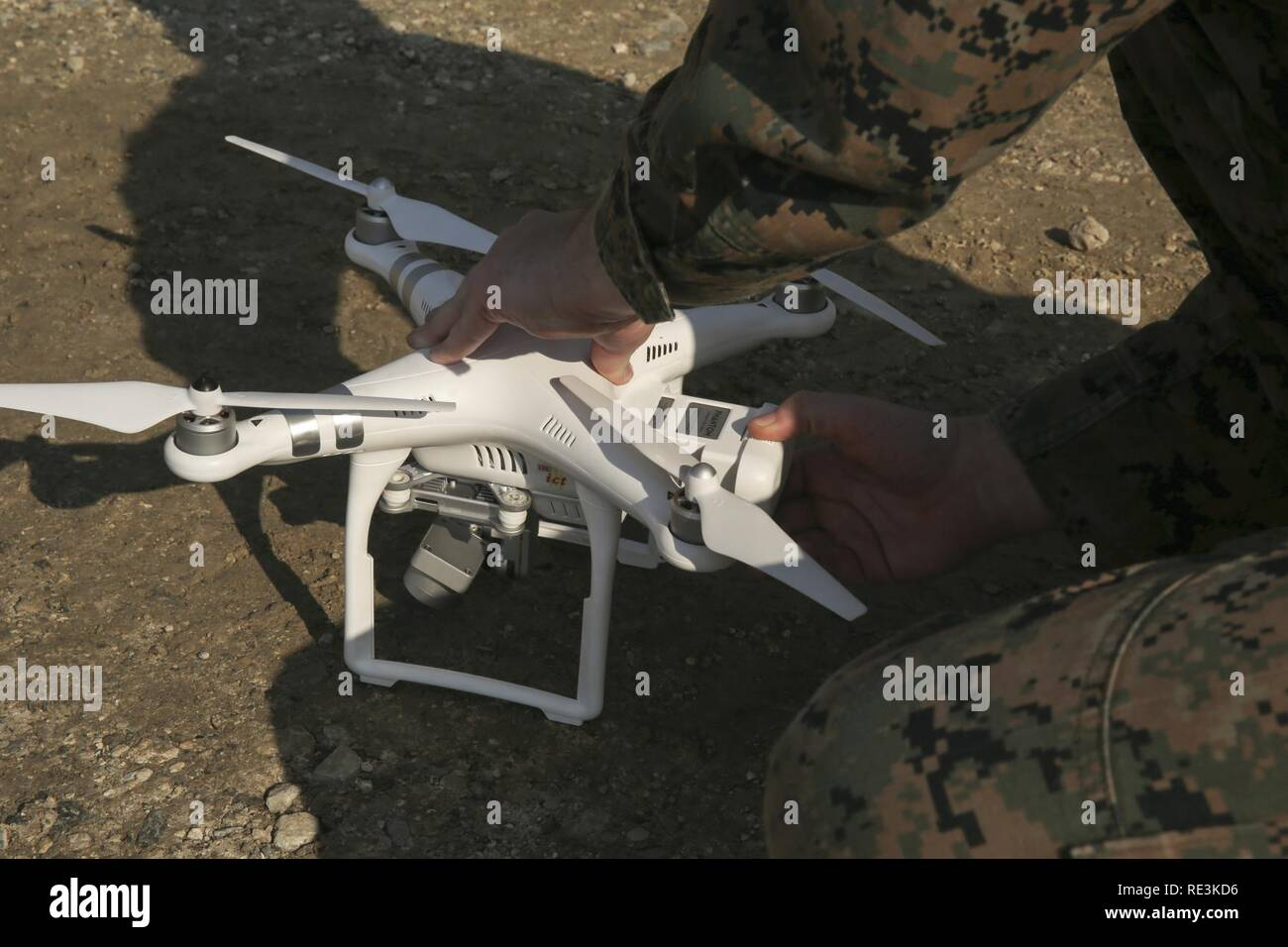 A Marine replaces a battery in the DJI Phantom 3 drone during a