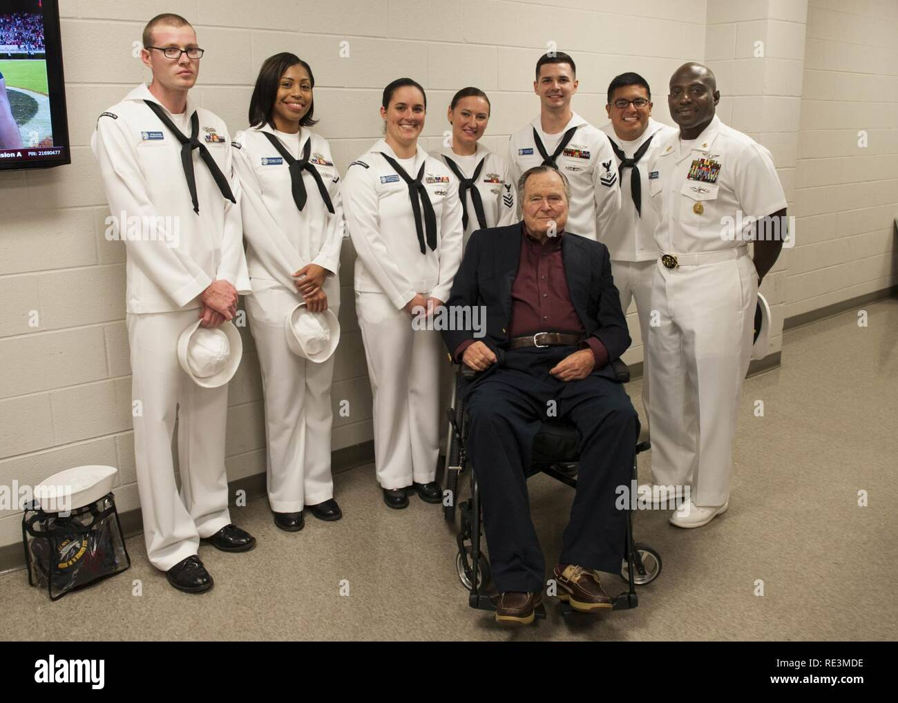 (COLLEGE STATION, Texas) Former President George H.W. Bush poses for a portrait with Sailors assigned to USS George H.W. Bush (CVN 77) during a military appreciation football game at Texas A&M University. The game is part of a two-day namesake trip to Texas where Sailors engaged with the local community about the importance of the Navy in defense and prosperity. Stock Photo
