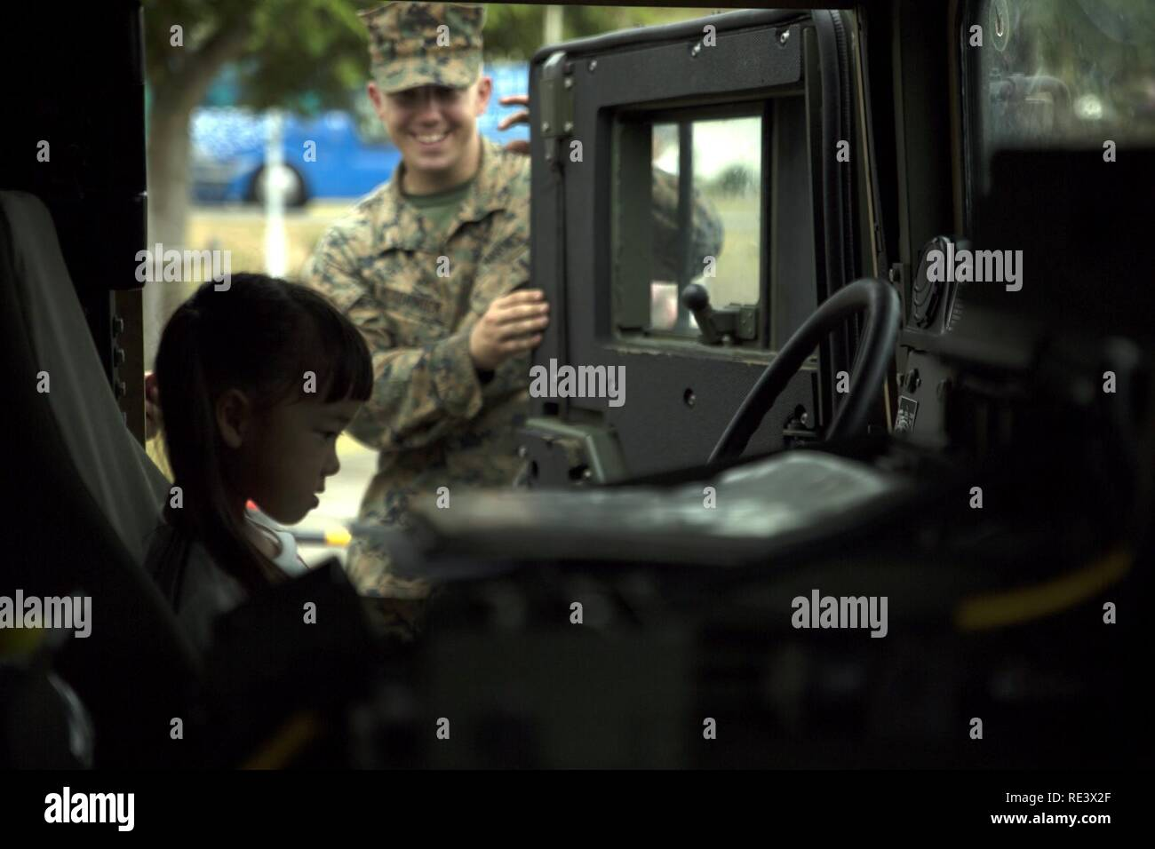 An Okinawa resident sits in a Humvee Nov. 20, 2016 during the Japan Ground Self-Defense Force Festival on Camp Naha, Okinawa, Japan. The festival celebrated the 6th anniversary of the 15th Brigade and the 44th anniversary of Camp Naha. The Humvee was one of three vehicles Marines with Combat Assault Battalion, 3rd Marine Division, III Marine Expeditionary Force brought for display. Stock Photo