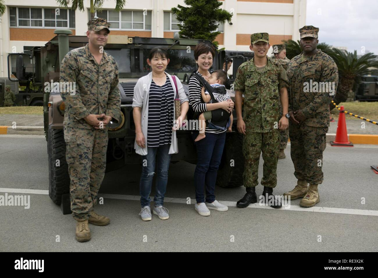 A family poses with Marines and a Japan Ground Self Defense Force service member next to a Humvee Nov. 20, 2016 during the JGSDF Festival on Camp Naha, Okinawa, Japan. The festival celebrated the 6th anniversary of the 15th brigade and the 44th anniversary of Camp Naha. Marines with Combat Assault Battalion, 3rd Marine Division, III Marine Expeditionary Force brought the Humvee, a Light Armored Vehicle and an Assault Amphibious Vehicle for display. Attendees of the festival were able to take photos with the Marines and their vehicles. Stock Photo