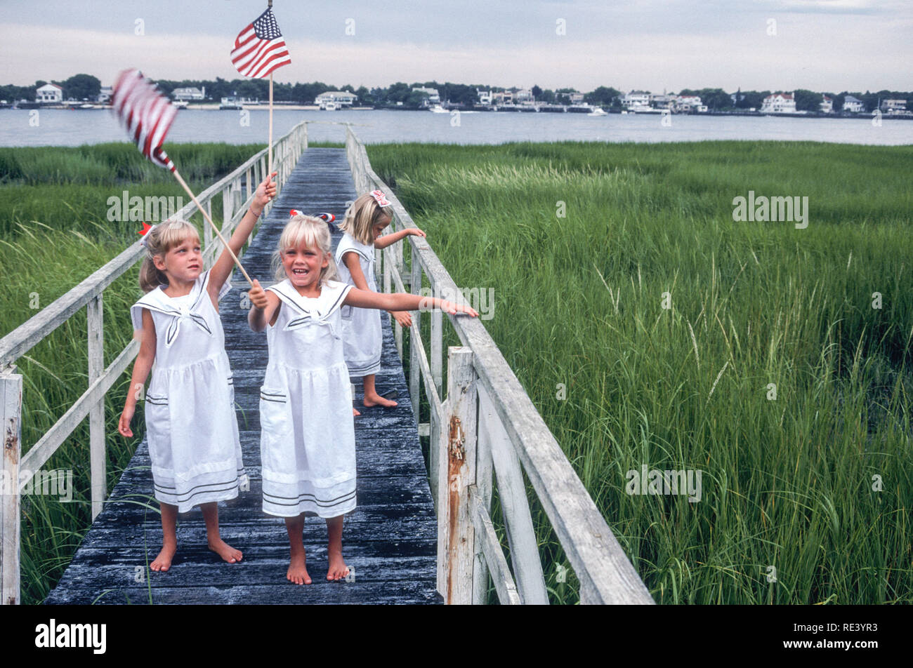 Identical Six Year Old Triplet SistersWaving Flags on the 4th of July, USA - Stock Image