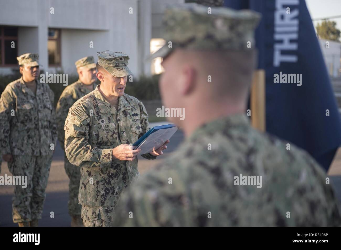 Capt. Jeffrey Kilian, commodore, 30th Naval Construction Regiment, reads a citation awarding the Meritorious Unit Commendation to 30 NCR for the regiment's efforts in providing command and control of Naval Construction Force units from July 2014, to March 2016. - Stock Image