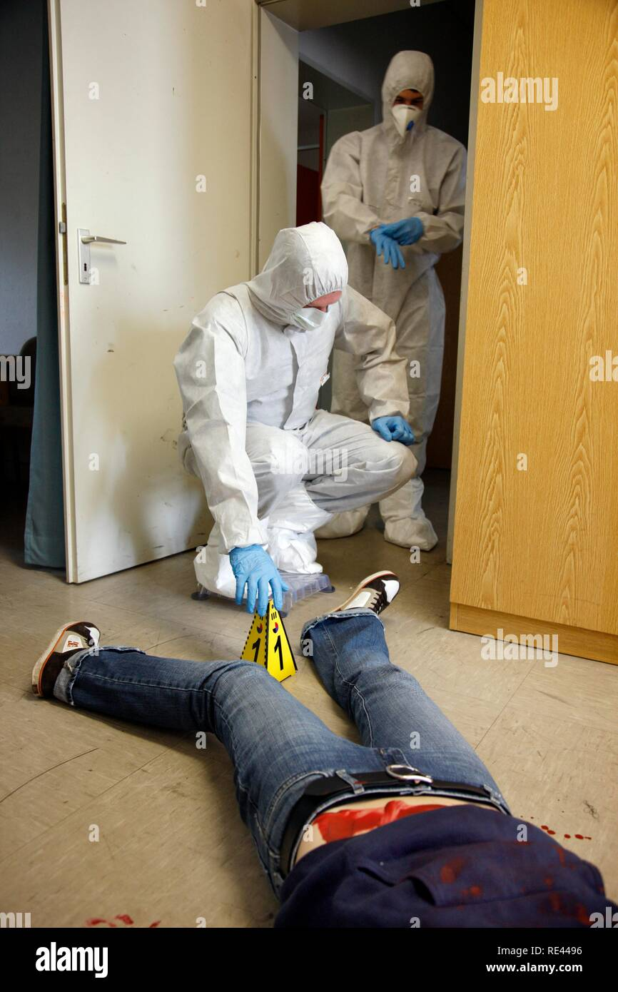 Officers of the C.I.D., the Criminal Investigation Department, gathering forensic evidence at a crime scene Stock Photo
