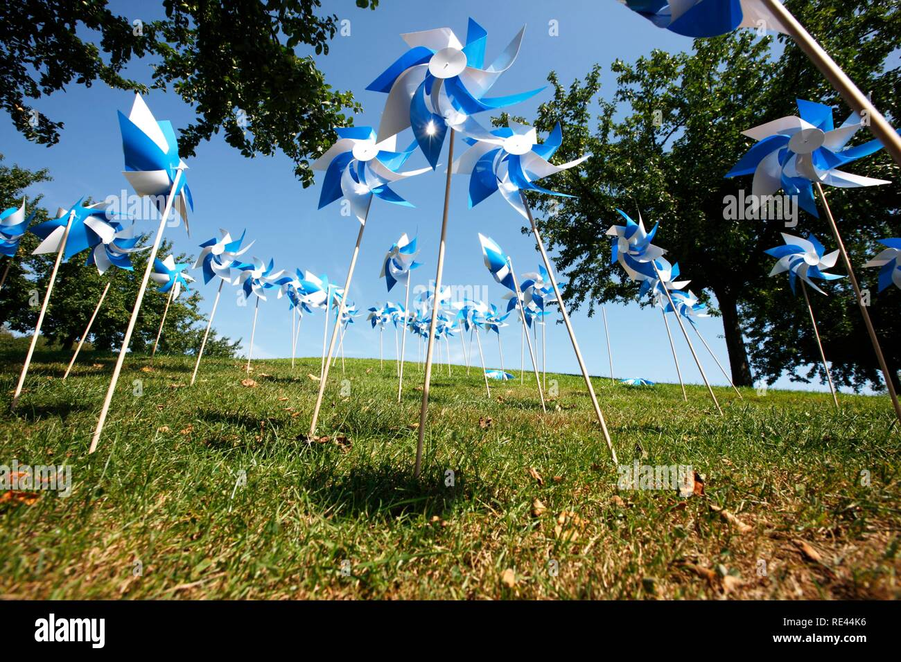 Blue and white plastic wind wheels as decoration on a lawn - Stock Image
