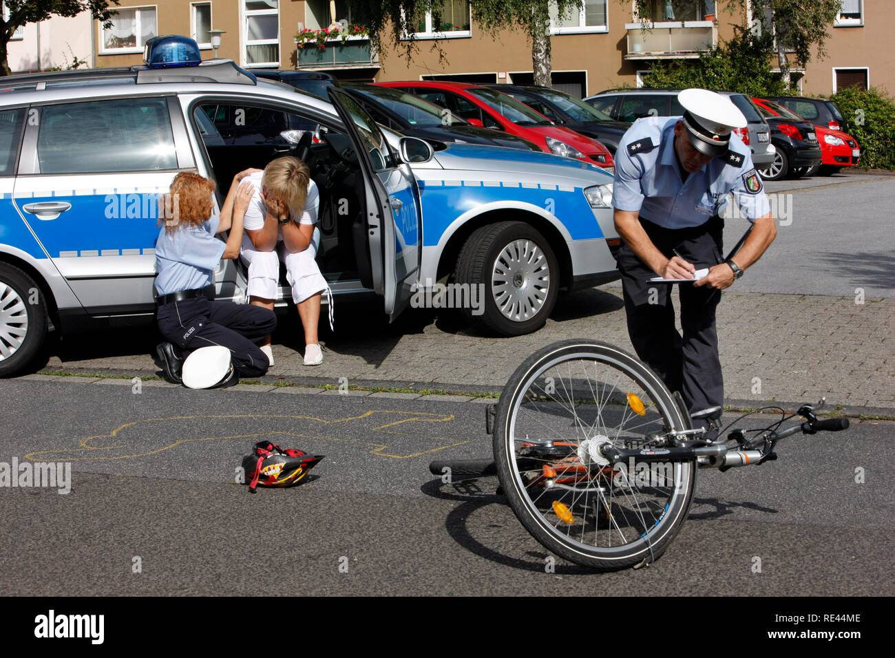 Police officers attend to the witness of a bicycle accident, victim support, emergency counselling, re-enactment - Stock Image