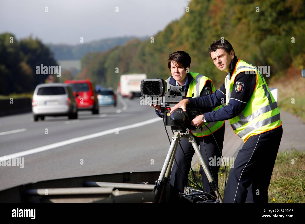 Police officers of the highway patrol errecting a radar measuring decice on the A2 highway for speed monitoring - Stock Image