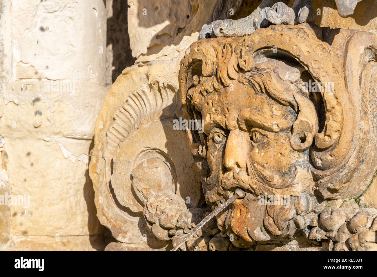 Closeup of a fountain in the shape of a face on St. Georges Square in Valletta, Malta - Stock Image