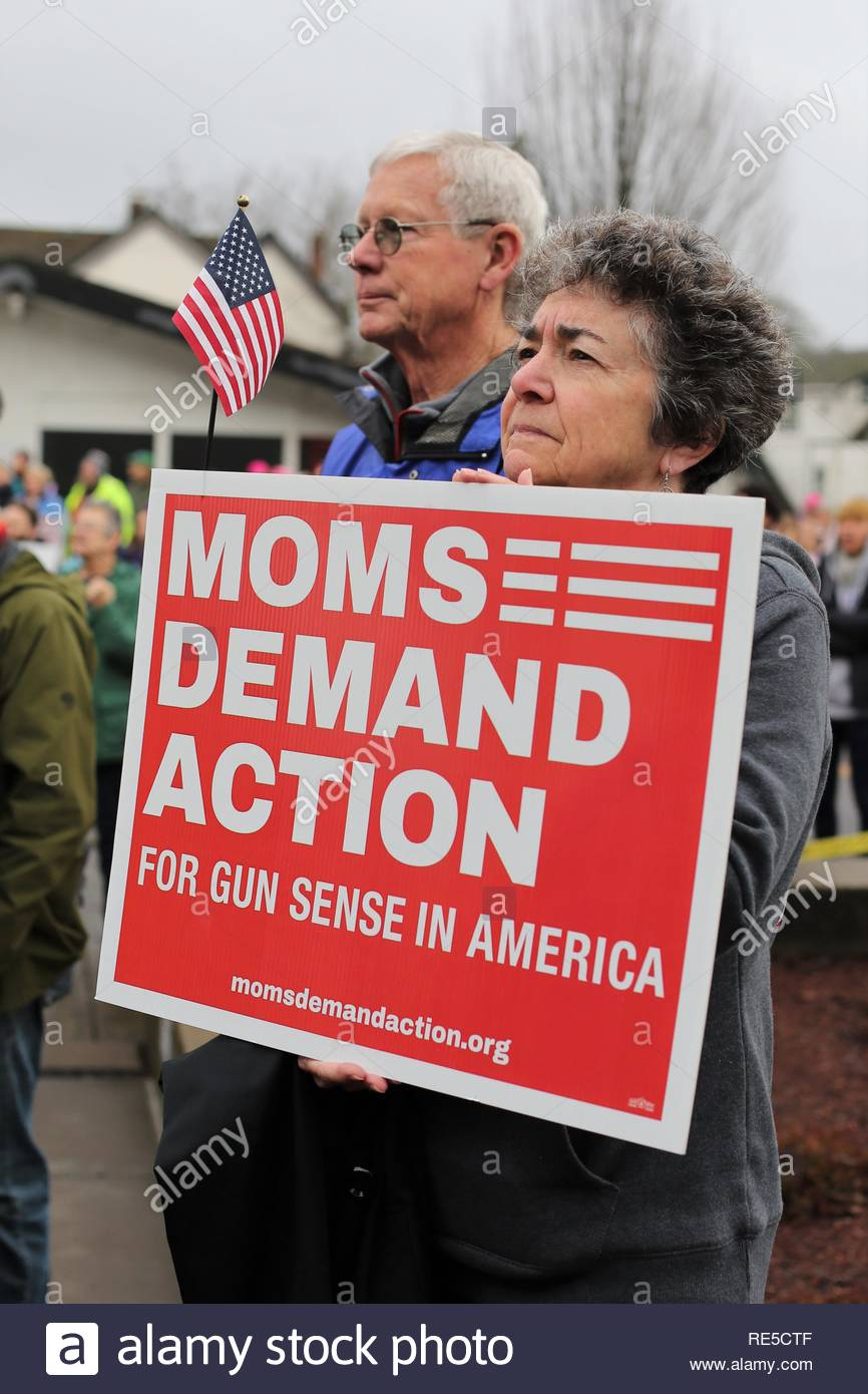 A woman holding a sign that reads 'Moms Demand Action for Gun Sense in America' at the Women's March in Eugene, Oregon, USA. - Stock Image