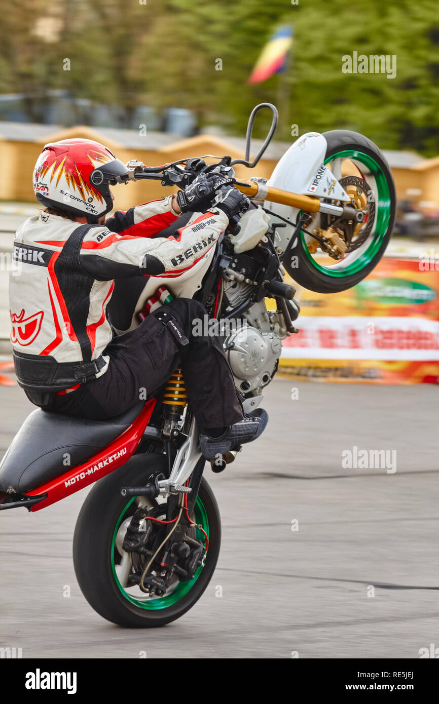 Bucharest, Romania - April 24, 2010: Professional motorcycle stunter Angyal Zoltan performs a sit down wheelie during the SMAEB event held at the ROME - Stock Image