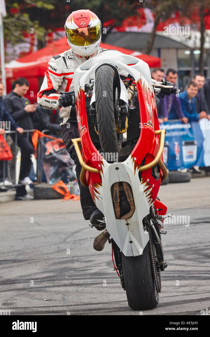 Bucharest, Romania - April 25, 2010: Professional motorcycle rider Angyal Zoltan performs a wheelie on his red and white sportbike during the SMAEB sh - Stock Image