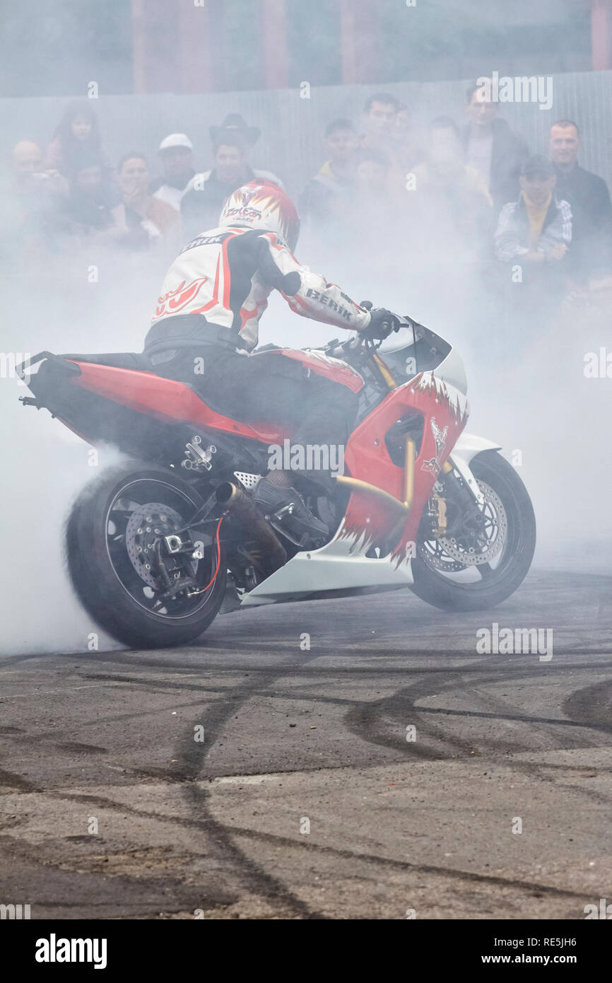 Bucharest, Romania - April 25, 2010: Professional motorcycle rider Angyal Zoltan performs a burnout on his red and white sportbike during the SMAEB sh - Stock Image