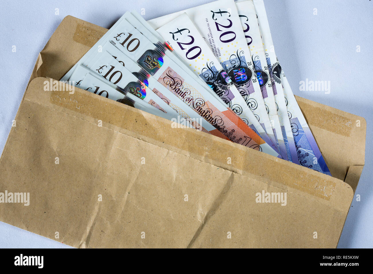 Brown envelope stuffed with English Ten and twenty pound notes. - Stock Image