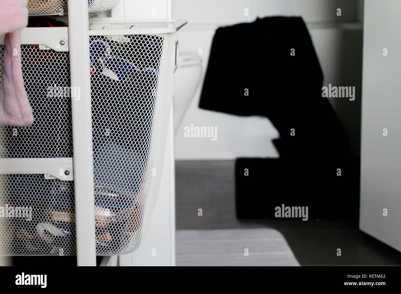 Clothes in closet drawer basket organizers, with bathroom in the background, and black towel hanging over bath tub. - Stock Image