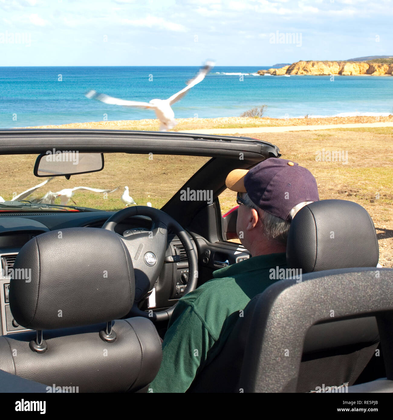 Man sitting in a car watching the beach - Stock Image