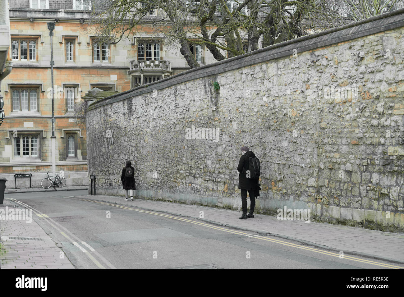 High stone wall of Jesus college, university of Oxford, England, abutting Ship street, with Exeter college in the background. - Stock Image