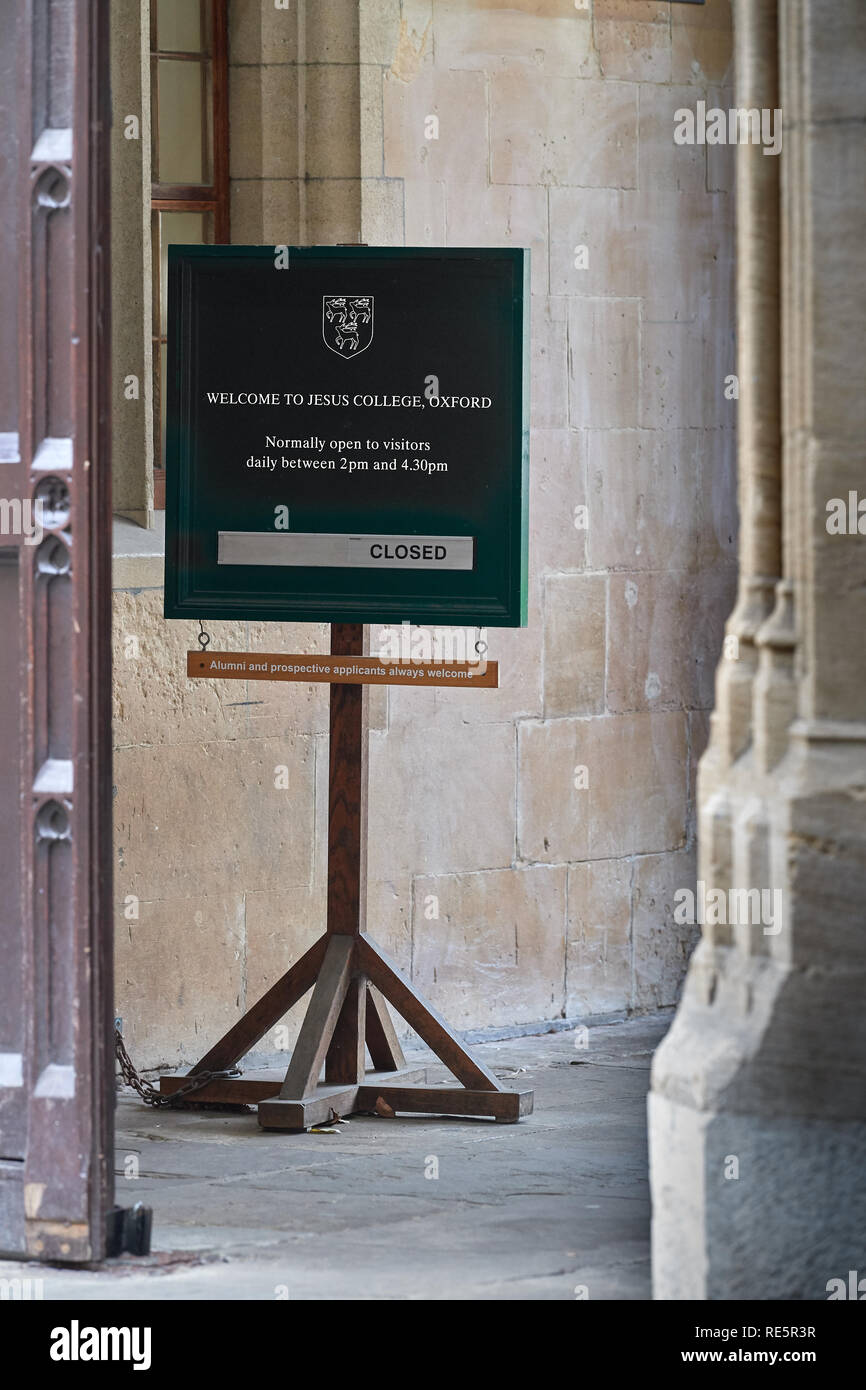 Notice at the entrance to Jesus college, university of Oxford, England, giving the times of visiting hours. - Stock Image
