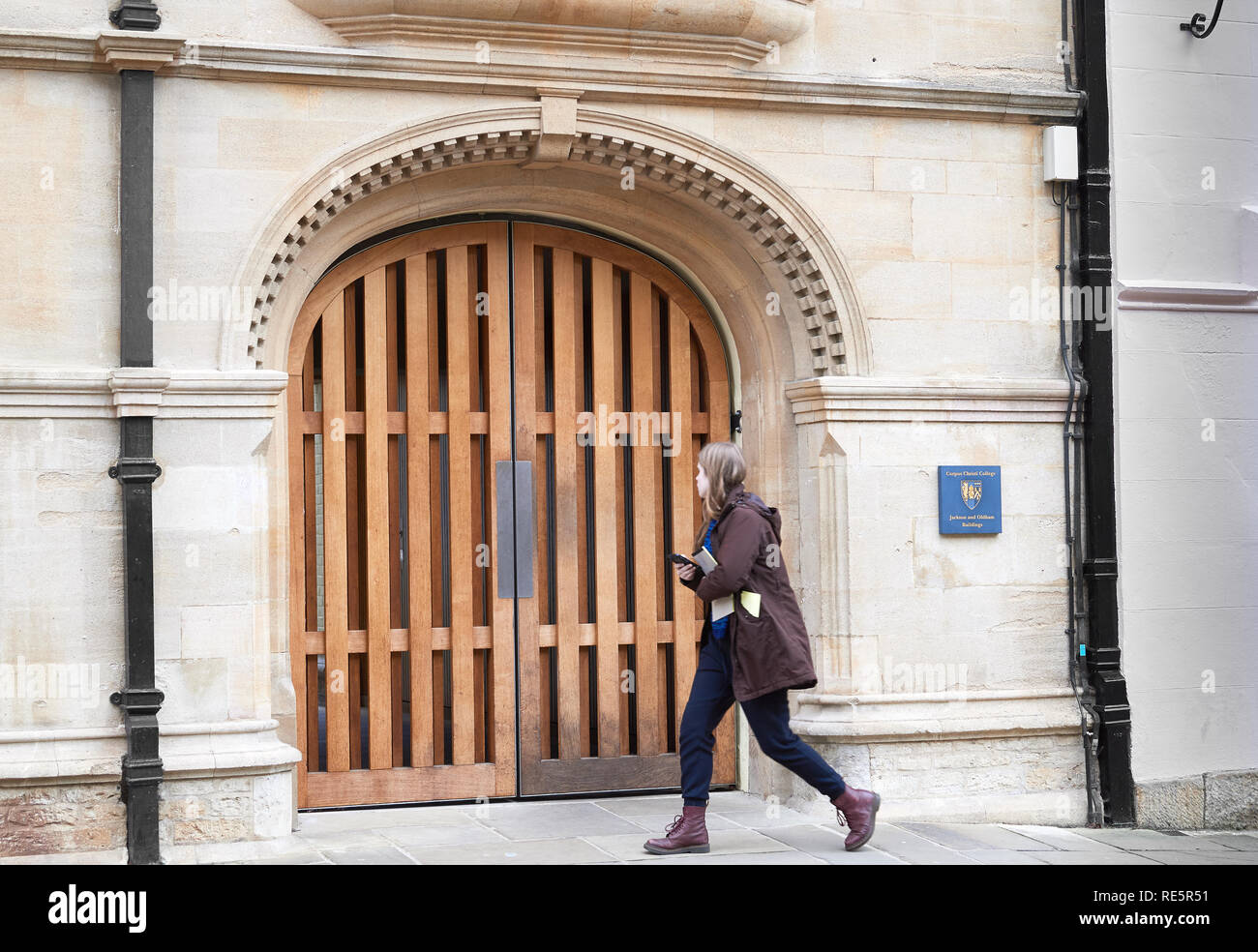 A female student walks pasts the gateway entrance to the Jackson and Oldham buildings of Corpus Christi college, university of Oxford, England. - Stock Image