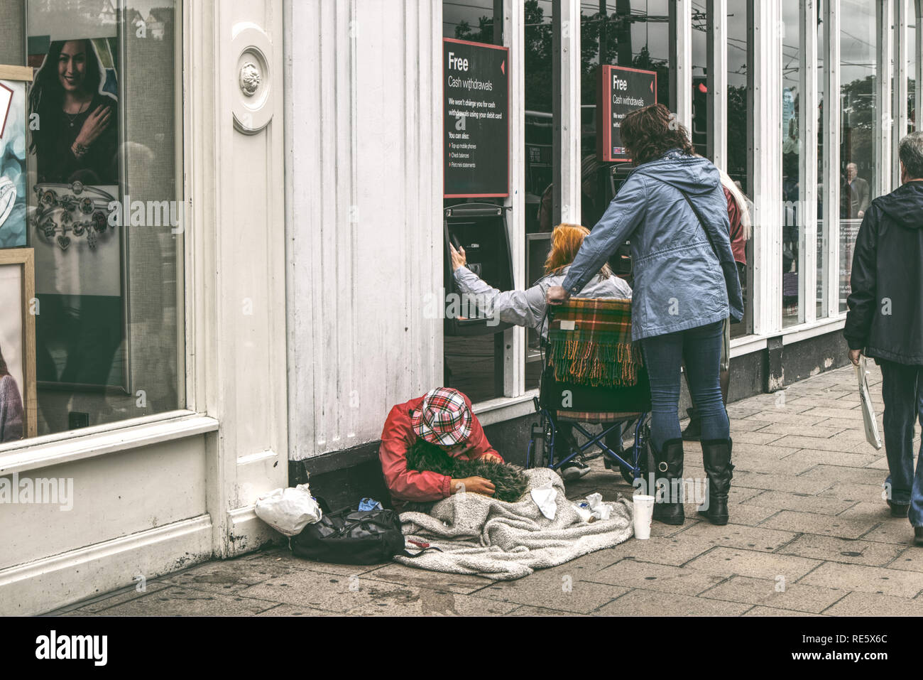 A man is begging on the street while a woman in a wheelchair is withdrawing cash on a high street in the UK - Stock Image