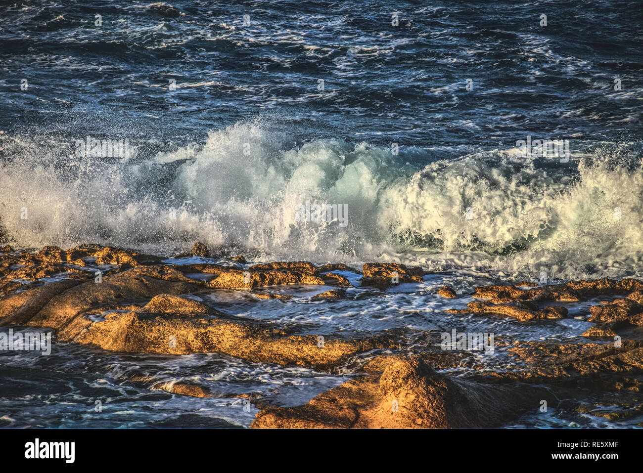Waves crashing with spray onto rocks on the shore at sunset - Stock Image