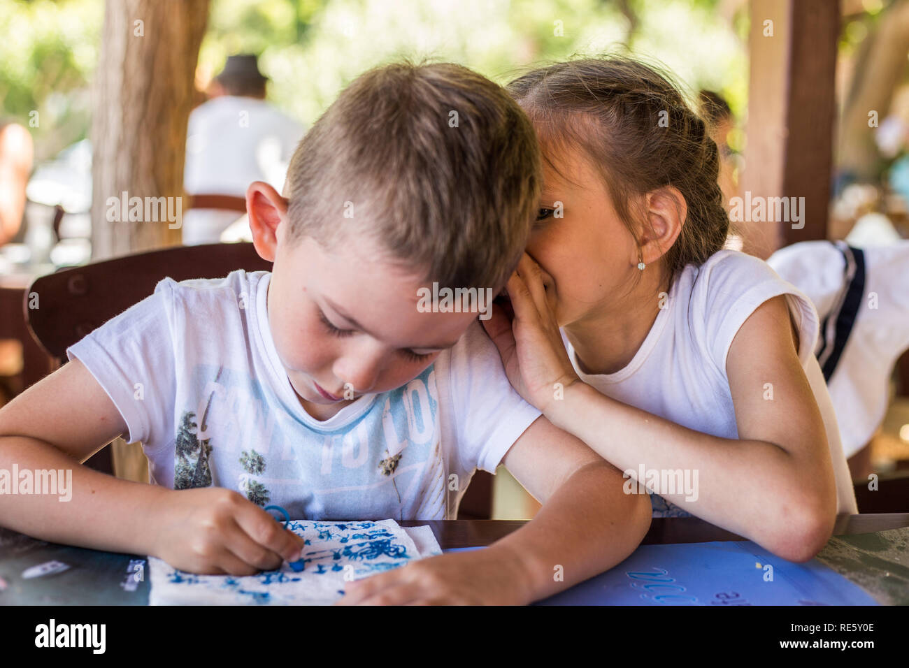 A little boy are whispering something to a pretty girl in a street restaurant. Children's friendship. Stock Photo