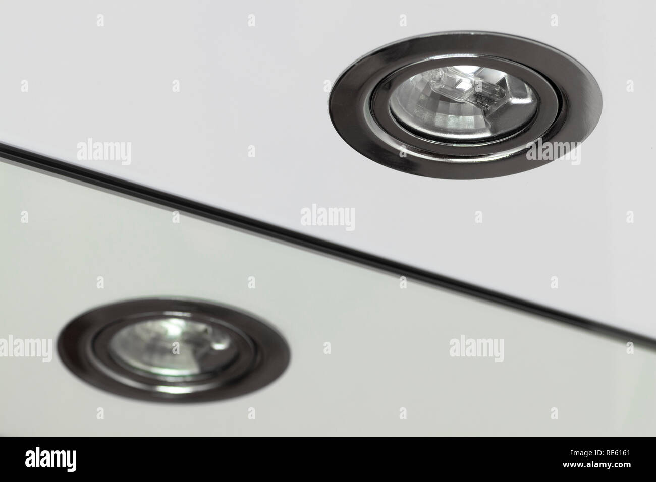 Recessed halogen lamp and reflection in the washbasin mirror. - Stock Image