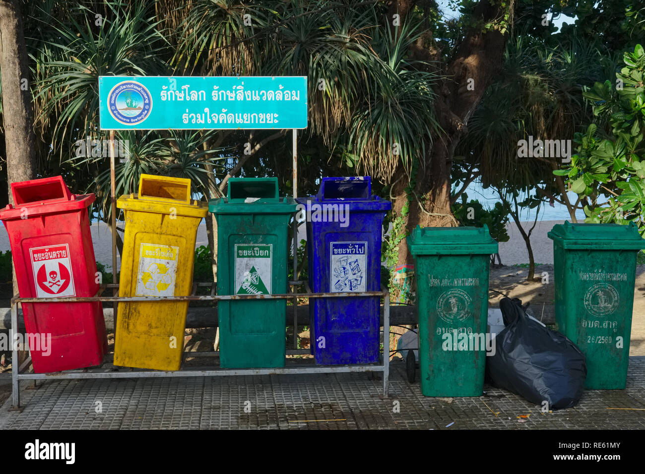 Trash cans at Nai Thon Beach, Phuket, Thailand, with different colors for different garbage, in an attempt to introduce trash separation - Stock Image