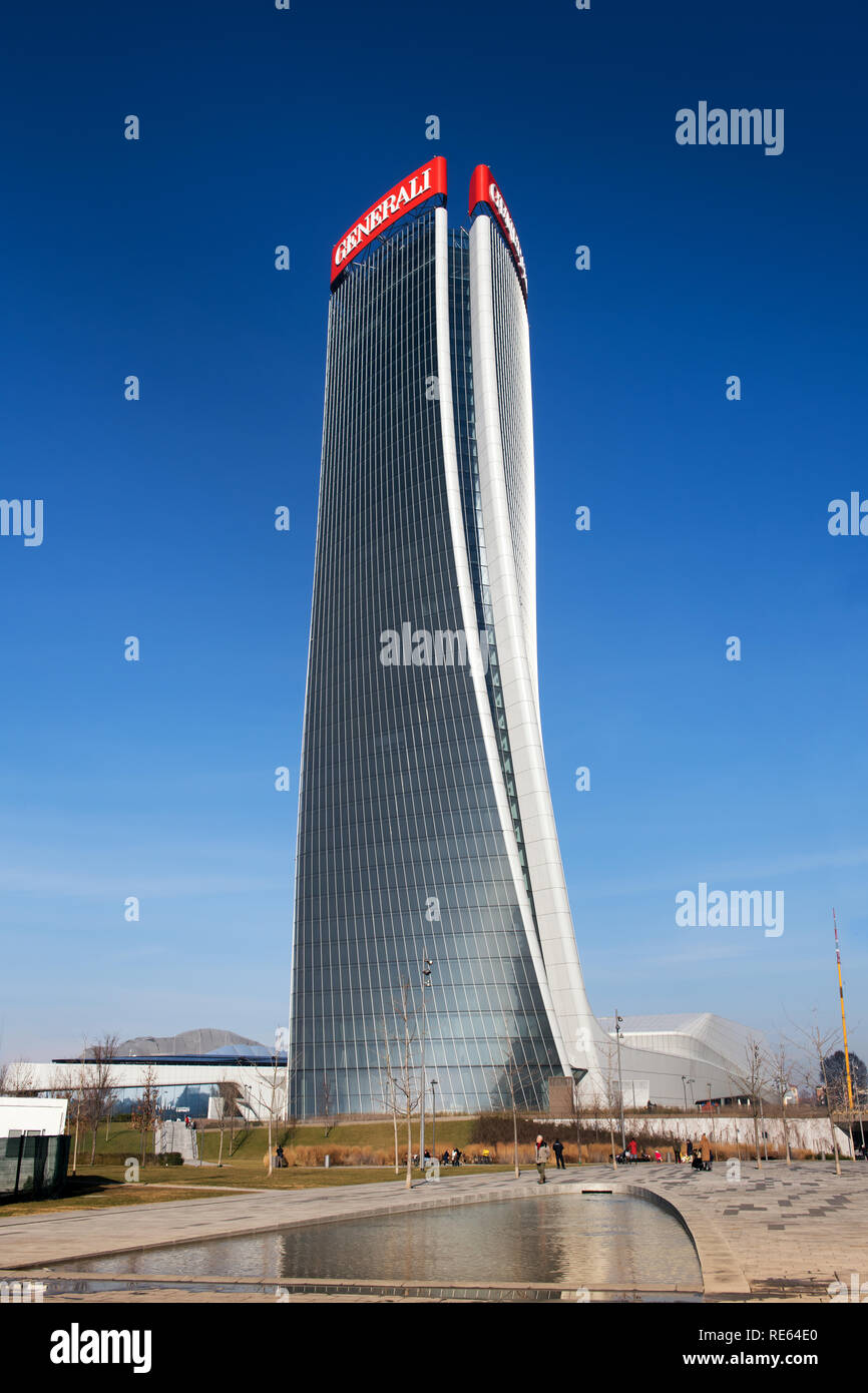 Exterior view of the Generali Tower, Milan with its distinctive warped design by architect Zaha Hadid reflected in a pool below against a blue sky Stock Photo