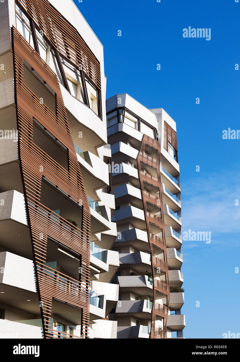 Timber cladding detail on modern apartment blocks with irregular warped angles on the building against a blue sky - Stock Image
