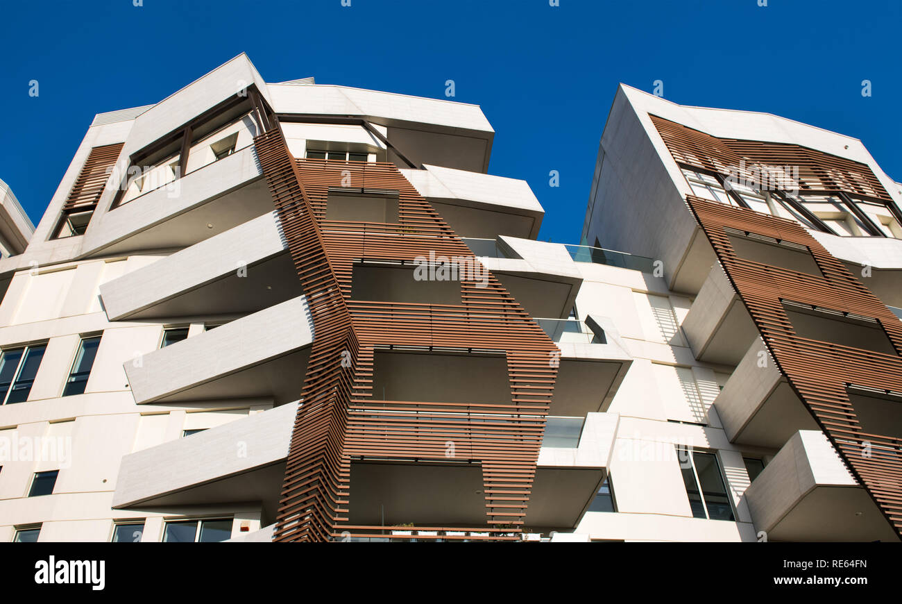 Modern angular design high-rise apartment blocks viewed from below showing external cladding against a blue sky - Stock Image