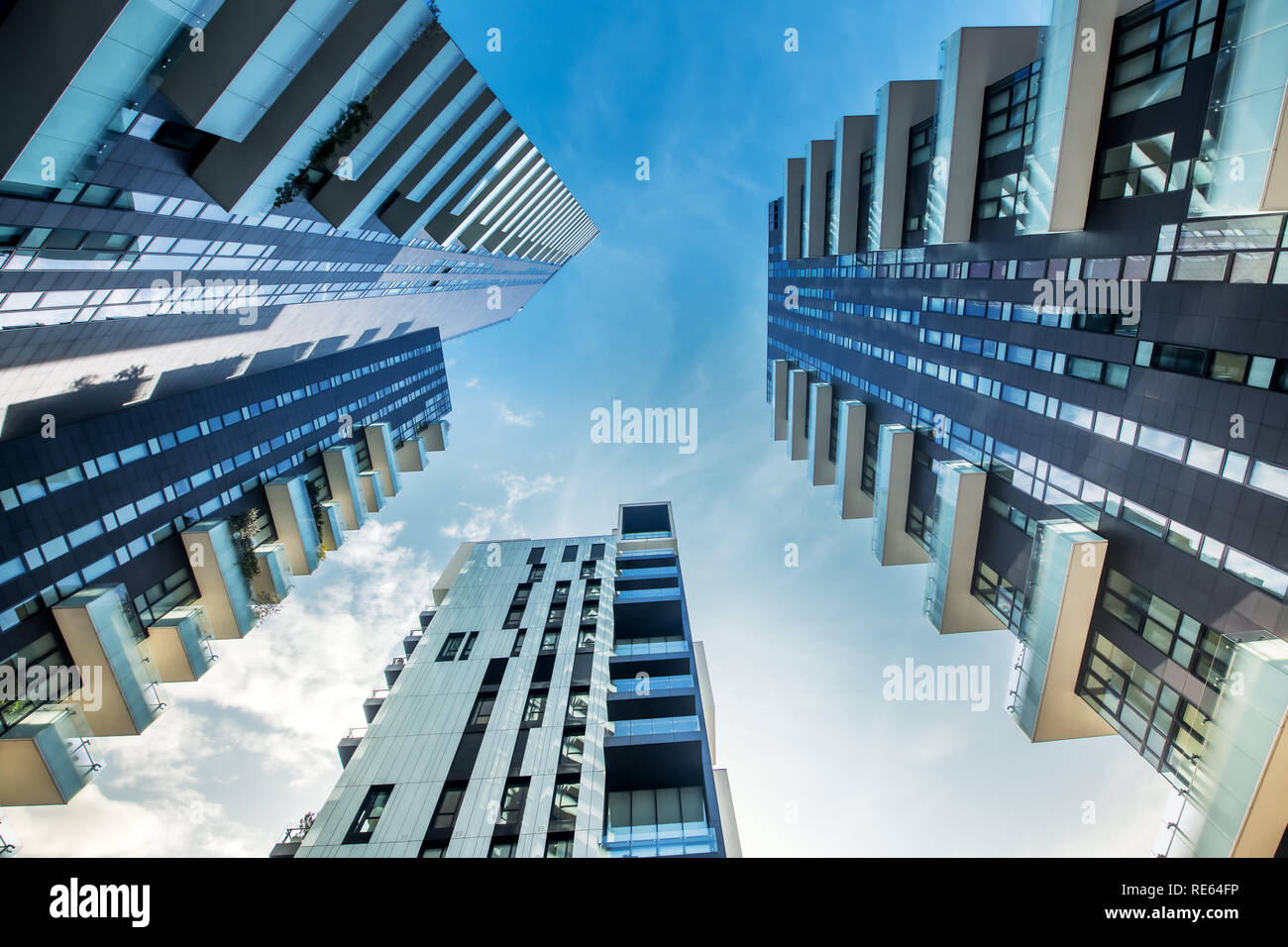 Low perspective view of modern Milan apartment blocks with large balconies looking up from below as they converge against a blue sky - Stock Image